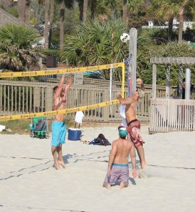 Guys playing beach volleyball